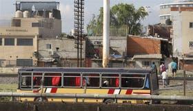 Uno de los colectivos ilegales se detiene en la calle Padre Mugica en la Villa 31; a la derecha, los pasajeros cruzan las vías con el consiguiente riesgo