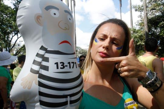 Una mujer sostiene un muñeco alusivo al ex presidente Lula mientras cientos de manifestantes se reúnen.