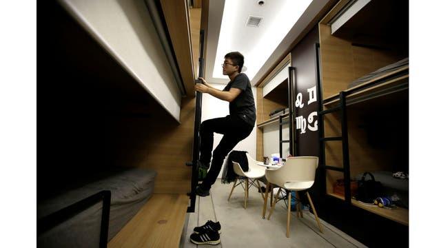Du Xianchang, un ingeniero de la empresa Baishan Nube, sube por una escalera a la cama en un cuarto individual para dormir en la oficina después de terminar el trabajo a media noche