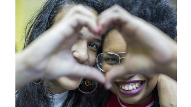 Elizabeth Cristina, 24 y Anna Bomfim , 26 hacen un corazón con sus manos luego de la celebración en la Iglesia Cristiana Contemporánea