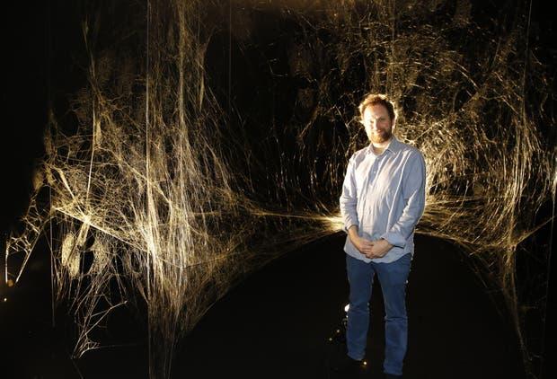 Tomás Saraceno junto a la tela construida por miles de arañas en el Mamba