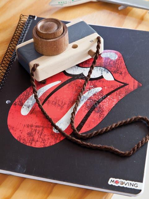 Sobre un cuaderno con tapa Rolling Stone ($49,90, Falabella), cámara de fotos de madera de Fanny y Alexander ($530, Stu).  /Magalí Saberian