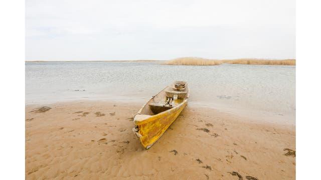 Un bote en la costa del mar de Aral en las afueras del pueblo de Karateren