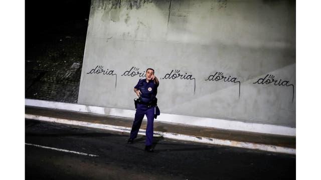 Un oficial de policía hace gestos hacia un artista brasileño, conocido como Iaco, después de haber escrito