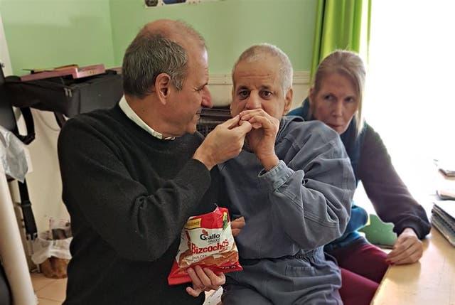 Julio le alcanza una galletita a Guillermo (derecha) en la sede de Checar
