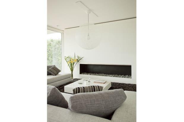 En el living dominan las formas rectangulares: en sillones, alfombra (todo Walmer) y mesa ratona (Joaquina D Amico) como en la chimenea. Lo único que desentona con el planteo es la lámpara de techo (Gris Dimensión).