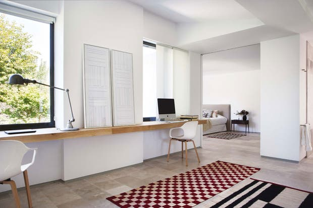 Dinámicas y coloridas, otras dos alfombras de la colección 'Mélange' –diseño de Sybilla para Nani Marquina– conectan espacios de usos disímiles. Como escritorio, un estante de madera maciza para trabajar de cara al jardín.  /Belén Imaz, gentileza Estudio Ábaton
