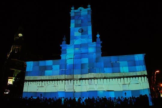 La bandera argentina, reflejada mediante una proyección basada en mapping, en las paredes del frente del Cabildo. Foto: DyN