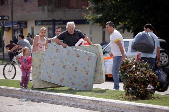 Un hombre lleva colchones que recibió por las donaciones. Foto: LA NACION / Silvana Colombo
