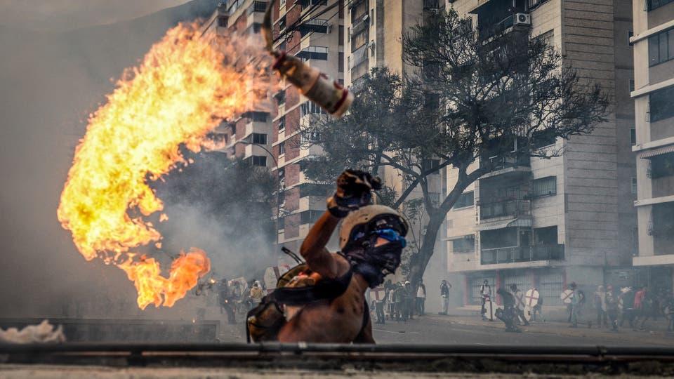Manifestantes chocan contra la policía antidisturbios en Caracas. Foto: AFP / Federico Parra