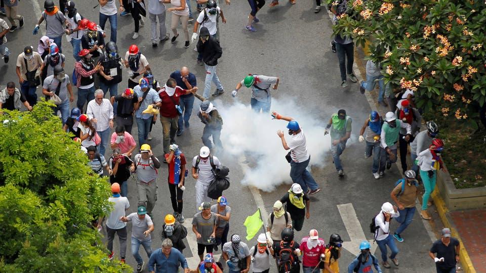 Los manifestantes se cubren de los gases arrojados por la policía. Foto: Reuters / Christian Veron