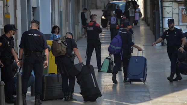 La policía nacional abandona el hotel y pasa frente a los Mossos, la fuerza regional catalana