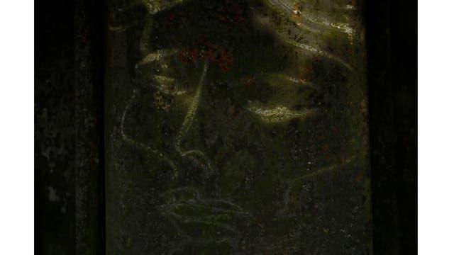 Un dibujo de una cara se ve en una pared de la orilla