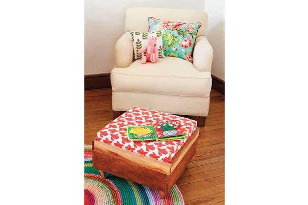Una banqueta tapizada con base de madera (Kom) frente al sillón (Lista Propia) y, debajo, el detalle de los almohadones floreado (Fan) y de lino con estampa ($125, Kom) y un oso traído de Nueva York..