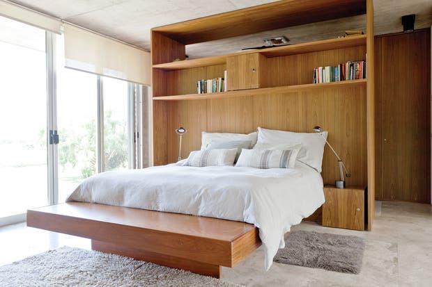 mueble que contiene la cama fue proyectado a medida en madera de incienso. El respaldo sirve como espacio de guardado y del otro lado funciona como un completo vestidor..