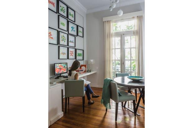 """Sobre la mesa laqueada que sirve de escritorio, Lori ubicó una serie de sus acuarelas sobre papel enmarcadas. En la pared opuesta, se impone el acrílico de 2x2 que se ve en la apertura, """"Variedades en un mundo infinito"""".  /Daniel Karp"""