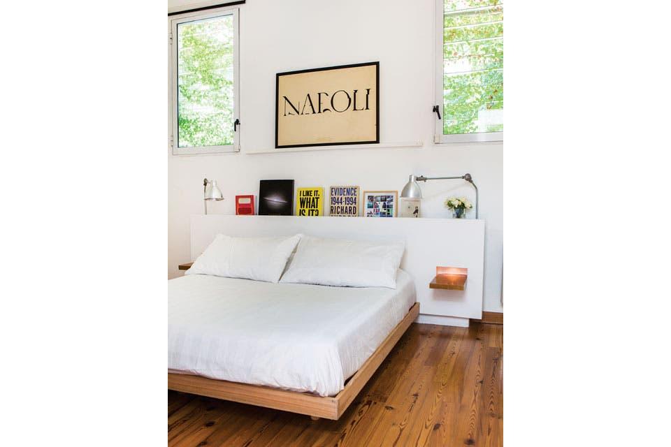 En la suite, cama baja de madera con acolchado blanco. La cabecera se hizo con una placa de MDF retirada un par de centímetros de la pared, con dos sencillísimos planos de madera a modo de mesas de luz. Enmarcada, una serigrafía de Pentagram Design.  Foto:Living /Santiago Ciuffo