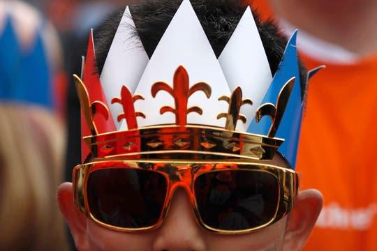 Con carteles y disfraces alusivos a la dinastía Orange, una multitud se congregó en la céntrica plaza Dam para darle la bienvenida a los nuevos reyes. Foto: Reuters