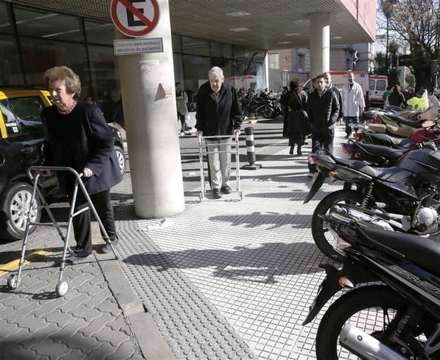 Personas con movilidad reducida sortean obstáculos en la vereda del hospital