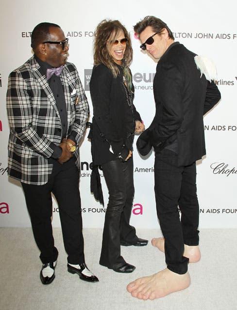 Divertidísimos: Jim Carrey hace reír a Randy Jackson y Steven Tyler con sus zapatos de pies gigantes y unas alitas de ángel. Foto: /Getty Images