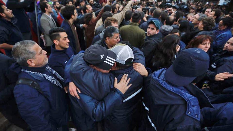 Dos trabajadores despedidos se abrazan al ser desalojados de la fábrica