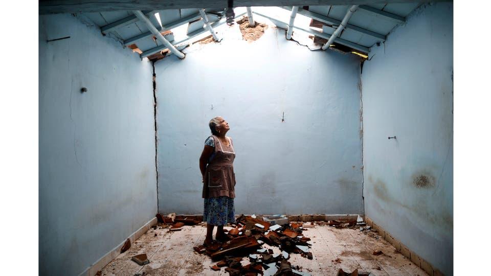 Tomasa Mozo, de 69 años, ama de casa, mira hacia el techo mientras posa para un retrato dentro de las ruinas de su casa después del terremoto en San José Platanar