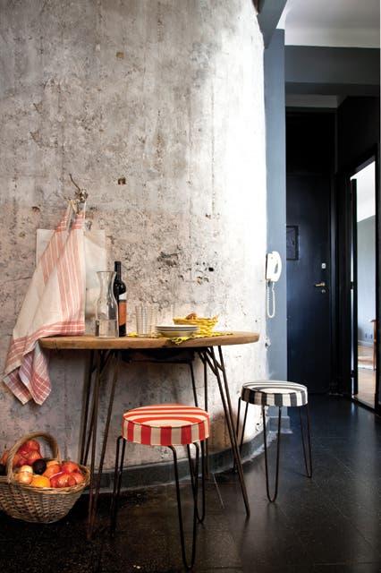 Para aprovechar el hall de entrada circular, se colocaron dos banquetas rayadas y una mesa con estructura metálica (todo de Mesopotamia Buenos Aires).  Foto:Living /Magalí Saberian