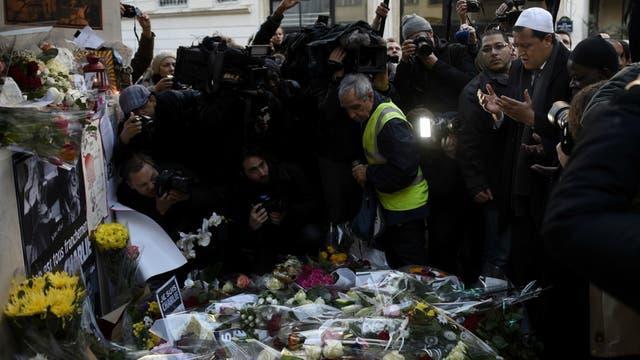 Un grupo de personas presta homenaje a las víctimas del atentado que mató 12 trabajadores de Charlie Hebdo en 2015