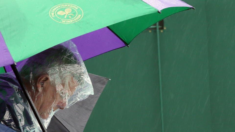 Un espectador se refugia bajo el paraguas  por lluvia  juegan en el quinto día de los campeonatos de tenis de Wimbledon en Londres, el viernes, 1 de julio de 2016.. Foto: AP / Tim Ireland