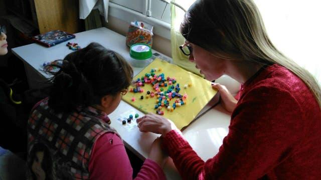 La Lic. Butus trabaja con una niña identificando y agrupando los colores