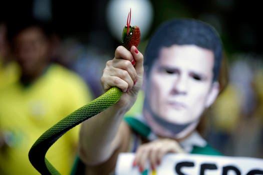Un manifestante mostraba una serpiente de juguete como forma de protesta. Foto: EFE