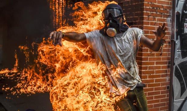 Un manifestante, entre las llamas tras la explosión de un tanque de combustible de un vehículo policial, en Caracas