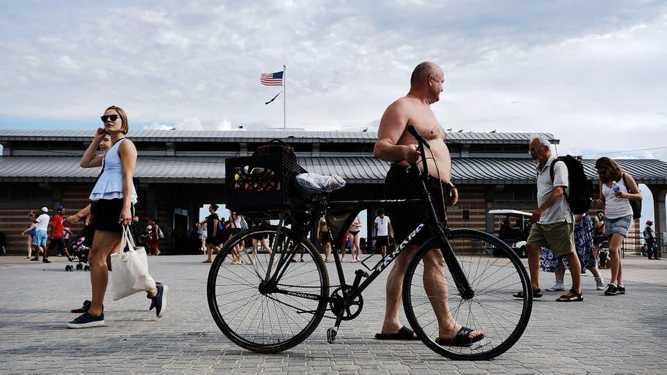 La gente recorre en el paseo marítimo en Coney Island en el primer día del verano en Nueva York. Después de una primavera inesperadamente húmeda, Nueva York ha estado experimentando días de cálidas temperaturas y sol brillante. Foto: AFP
