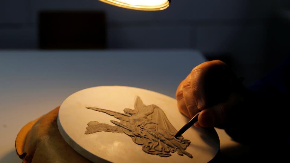 Nelson Carneiro, es el artesano de la Casa de la Moneda de Brasil y talla a mano el diseño de la medalla para hacer los moldes. Foto: Reuters / Sergio Moraes
