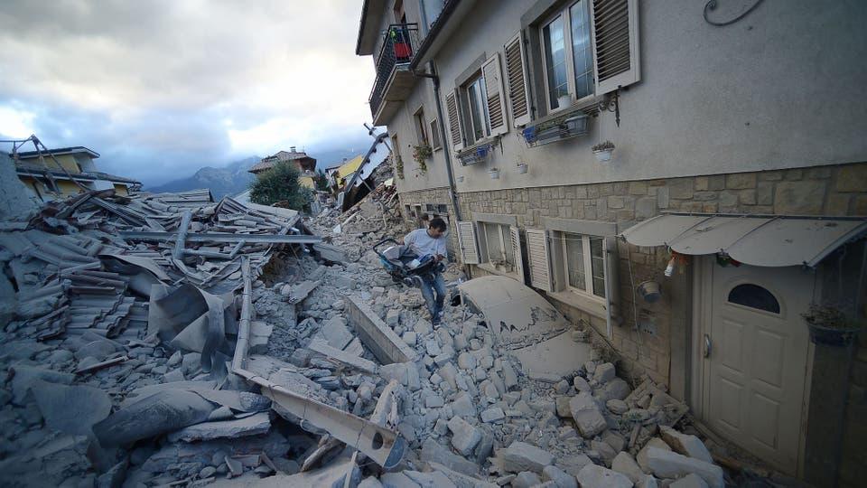 Un hombre camina entre los escombros en la puerta de su casa. Foto: AFP / Filippo Monteforte