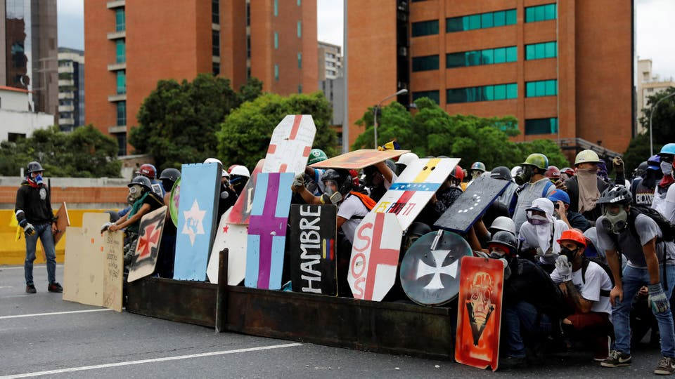 Los manifestantes se cubren con escudos para enfrentar a la milicia venezolana. Foto: Reuters / Carlos Garcia Rawlins