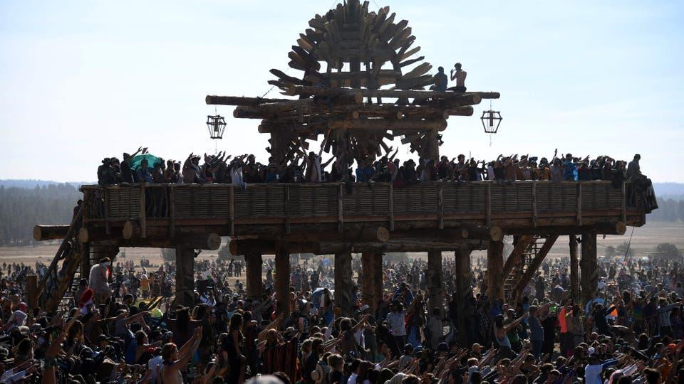 La gente ve el comienzo del eclipse y levanta sus brazos en oración