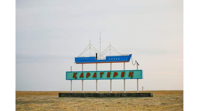 Un cartel con un barco y el nombre de un pueblo durante el atardecer fuera de la aldea de Karateren, cerca del mar de Aral, al sudoeste de Kazakhstan