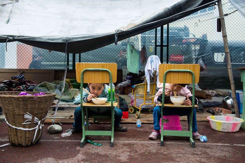 Los niños de la tragedia se alimentan en las carpas donde fueron evacuados junto a sus familias. Foto: AFP