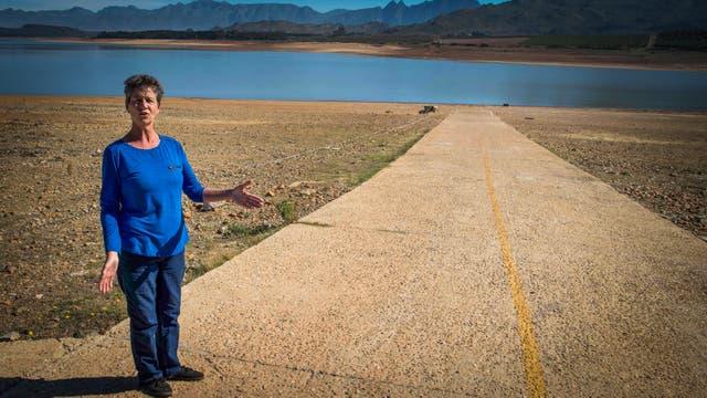 Lisa Wheeler, secretaria del Club Deportivo Theewaterskloof, muestra dónde se encuentra la marca de agua alta de la presa, que tiene menos del 20% de su capacidad hídrica