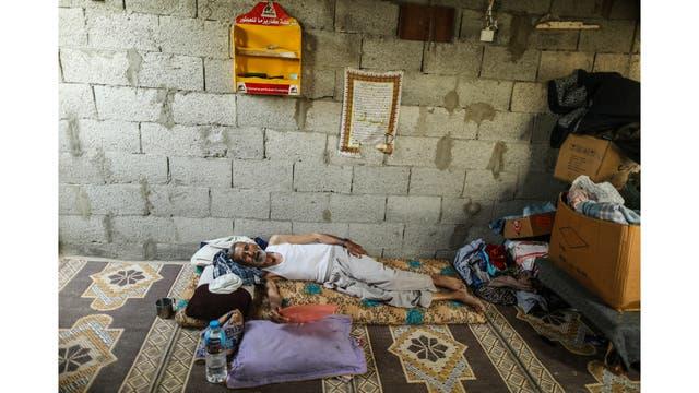 Un hombre usa una bandeja de plástico para ventilarse durante un corte de luz en su casa en Khan Younis, en el sur de la Franja de Gaza