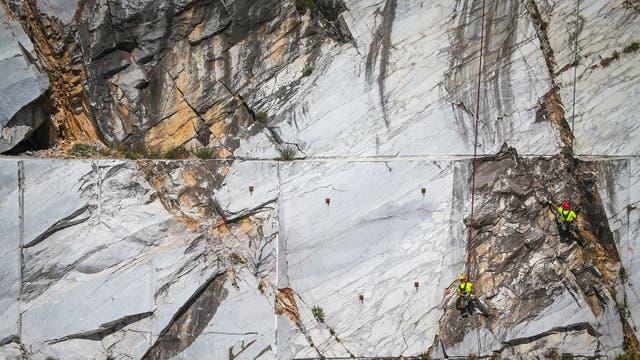 """Trabajadores, conocidos como """"Tecchiaiolo"""", examinan el mármol en la cantera de Cervaiole en Monte Altissimo en los Alpes Apuanos, Toscana"""