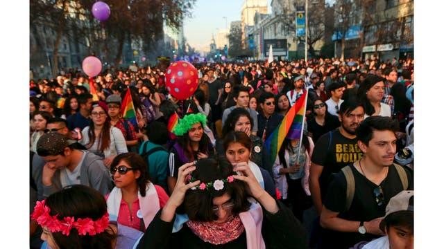 Angela, debajo del centro, coloca una corona de flores en su cabeza mientras asiste a una marcha del Orgullo Gay junto a otros niños transgéneros en Santiago, Chile