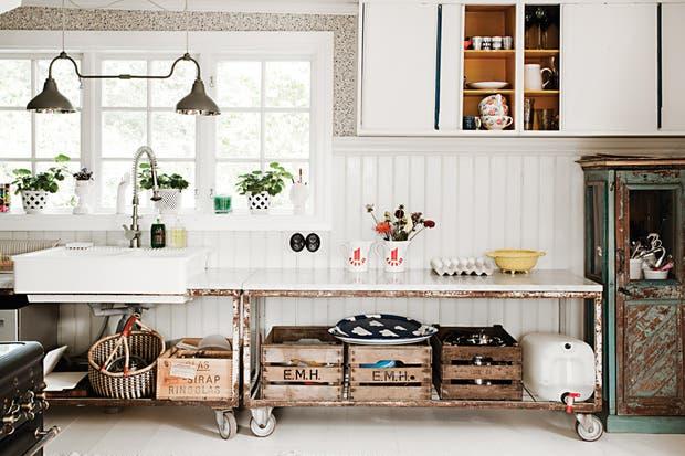 En la cocina, una amplia mesada sostenida por una vieja estructura de hierro que aporta un aire industrial y ofrece espacio de guardado con cajones de manzanas y otros personalizados (Plantabox)..