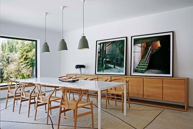 Mesa italiana 'Tense' (MDF), sillas 'CH 24', diseño de Hans Wegner (Carl Hansen), lámparas colgantes 'Caravaggio' (Light Years). Sobre el vajillero de roble (Ethnicraft) se apoya una lámpara de mesa 'Snoopy' (Flos) y fotos de Juan Baraja.  /Belén Imaz, gentileza Estudio Ábaton
