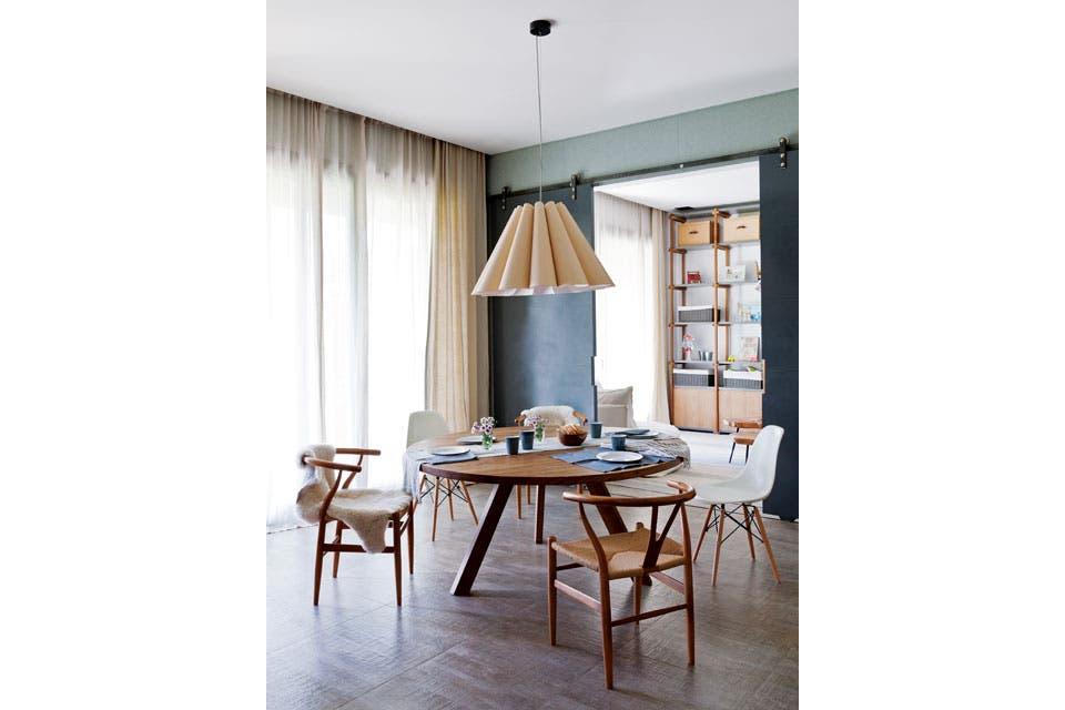 Ubicado junto a la cocina, el comedor diario tiene una mesa 'Mula' (Mesopotamia BA), una combinación de sillas Eames y 'Wishbone', lámpara colgante 'Lora' de Weplight (Iluminación Agüero) y cortinas en gasa de lino color piedra (LB Géneros).  Foto:Living /Magalí Saberian