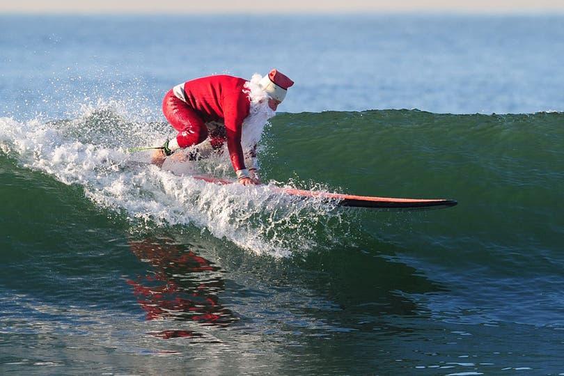 El afamado surfista Michael Pless en la previa de Nochebuena en Seal Beach, al sur de Los Ángeles. Foto: AFP