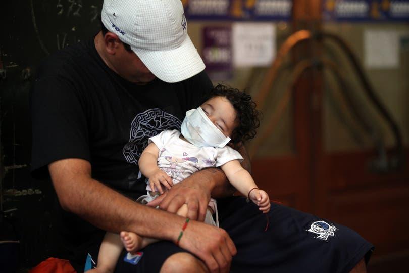 Un hombre sostiene a su bebe luego de colocarle un barbijo para protegerlo de la nube tóxica. Foto: LA NACION / Silvana Colombo