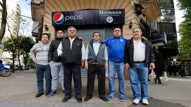 Un grupo de empleados del restaurante, hoy al mediodía, frente al local cerrado a la espera de novedades