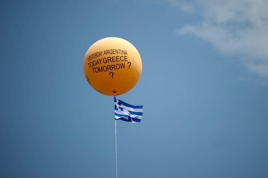 """""""Ayer Argentina, ahora Grecia, mañana?"""", se aprecia en un globo que sobrevuela Atenas, junto a una bandera griega. Foto: EFE"""